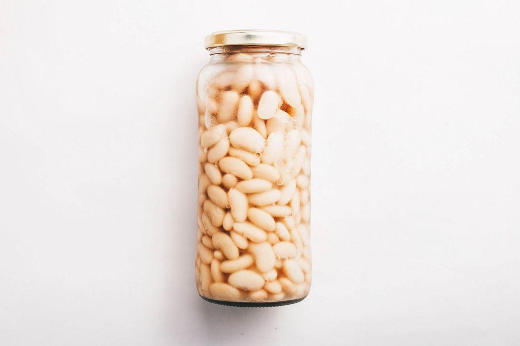 Weiße Bohnen im Glas vor weißem Hintergrund