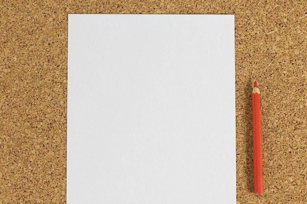 Weißes Blatt Papier mit rotem Bleistift auf einer Oberfläche aus Korken
