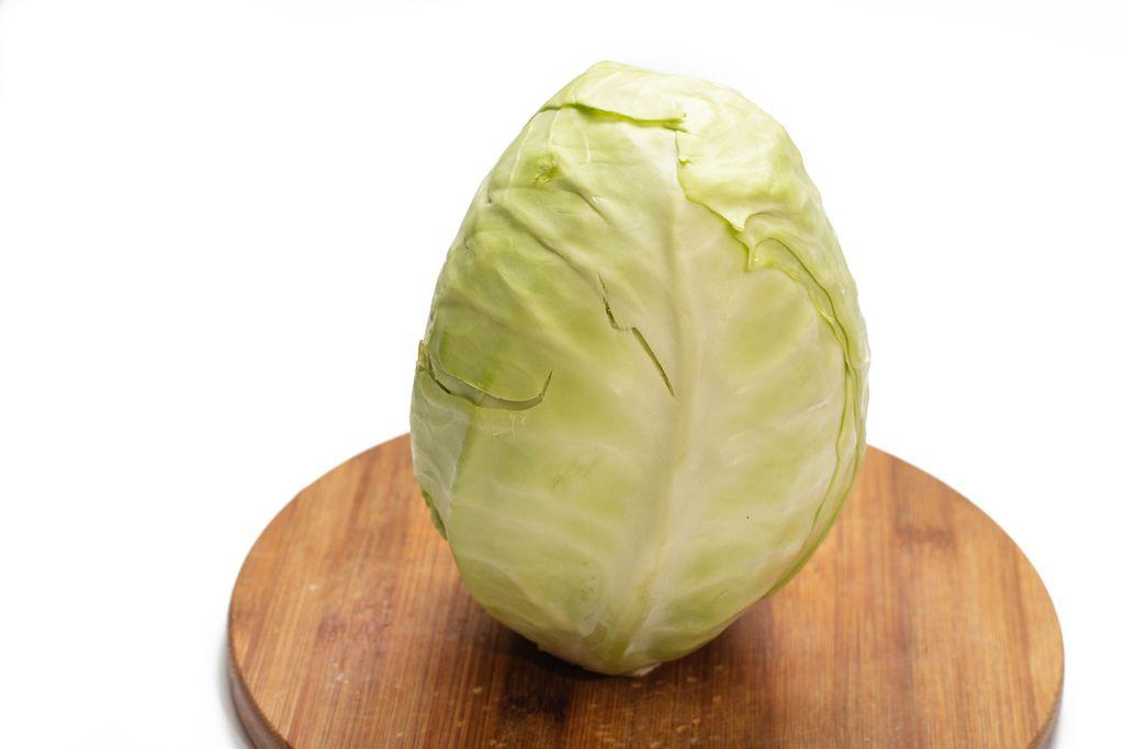 Weißkohl für Krautsalat steht auf hölzernem Küchenbrett isoliert vor weißem Hintergrund