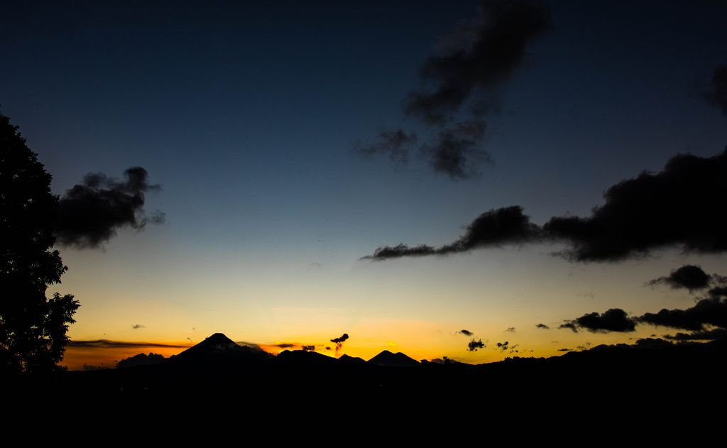 Weitwinkelaufnahme von einem farbenfrohen, orange und gelb leuchtenden Sonnenuntergang über den Vulkanen in Guatemala mit wenigen Wolken am Himmel