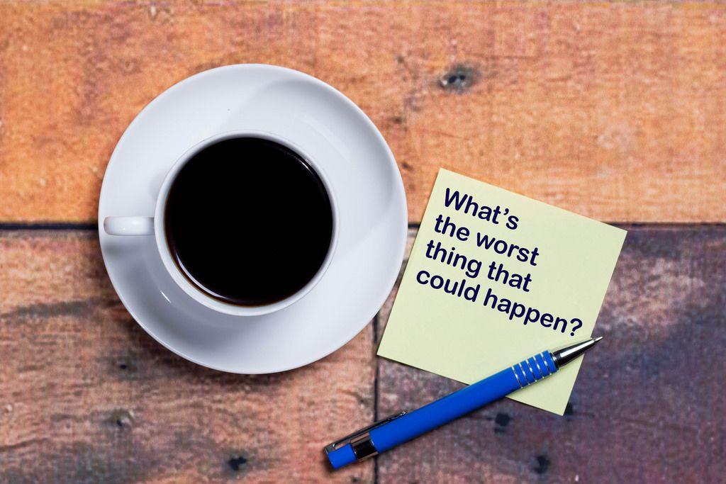 What's the worst thing that could happen? Was ist das schlimmste dass passieren könnte? Notiz mit Kaffeetasse