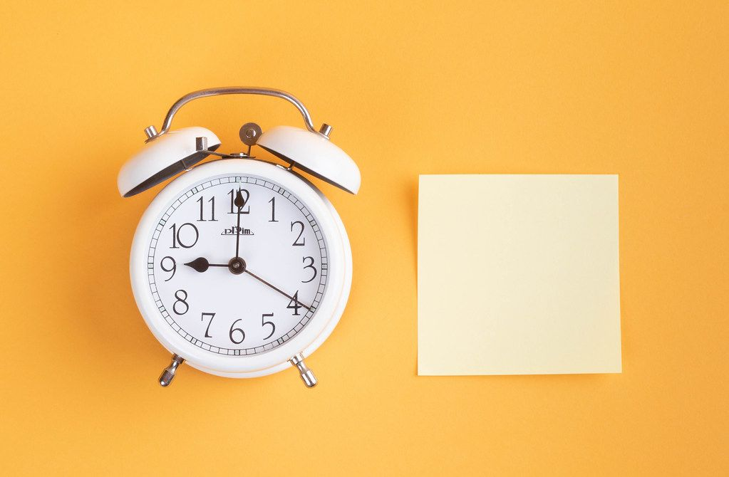 White alarm clock on yellow background with empty sticky note