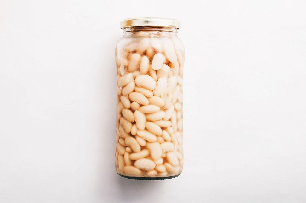 White beans in a jar on white background