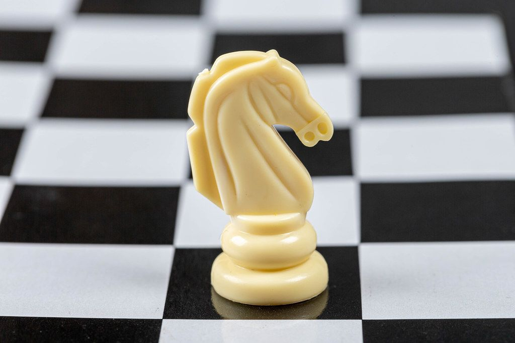 White chess horse piece on the board background (Flip 2019)