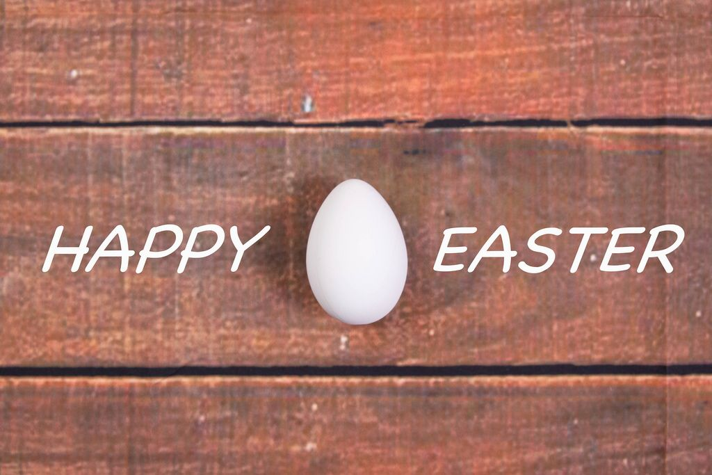 White chicken egg with Happy Easter text on wooden background