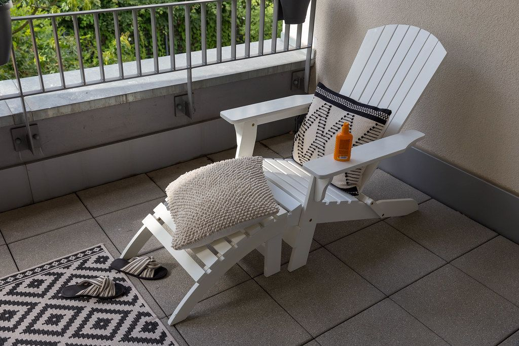 White deckchair - sun lounger -  with comfortable cushions, summer slippers and sun milk, on a balcony