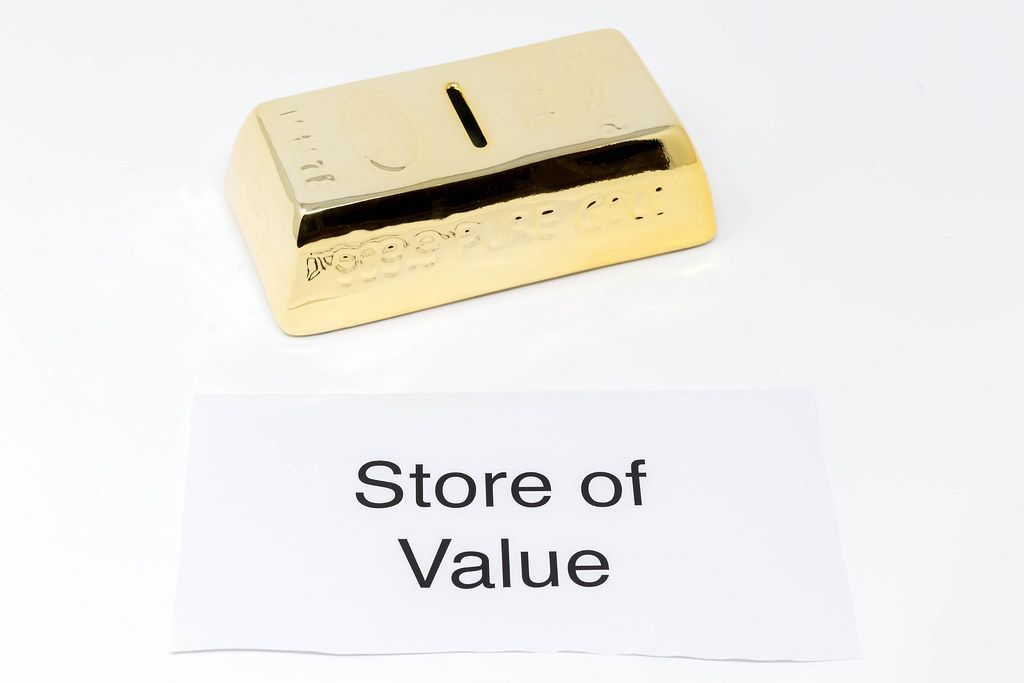 White paper with lettering STORE OF VALUE next to gold bars = gold as an investment object