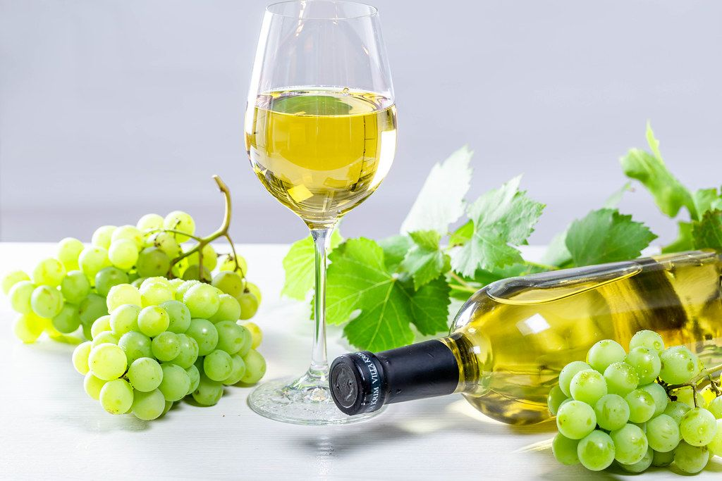 White wine in a glass with a full bottle, grapes and leaves on a white wooden background