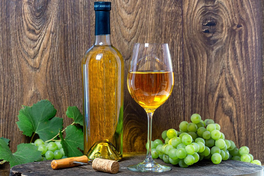 White wine with fresh grapes and corkscrew on brown wooden background (Flip 2019)