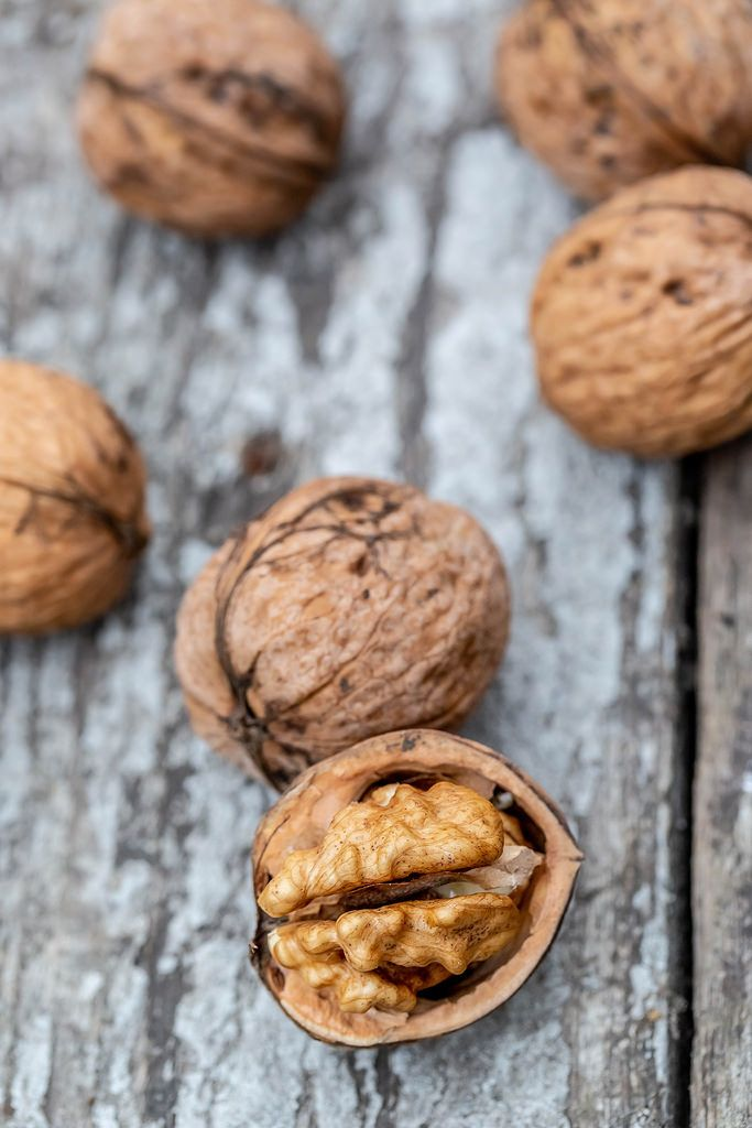 Whole and half walnuts on wooden background