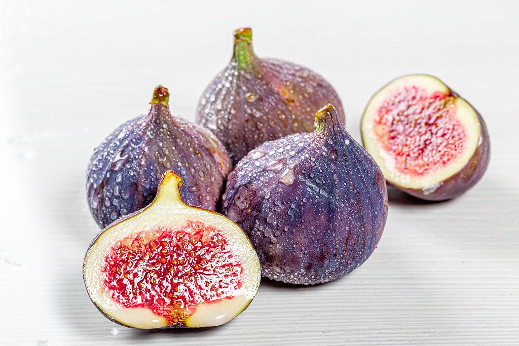 Whole and halves of fresh figs with water drops on white wooden background