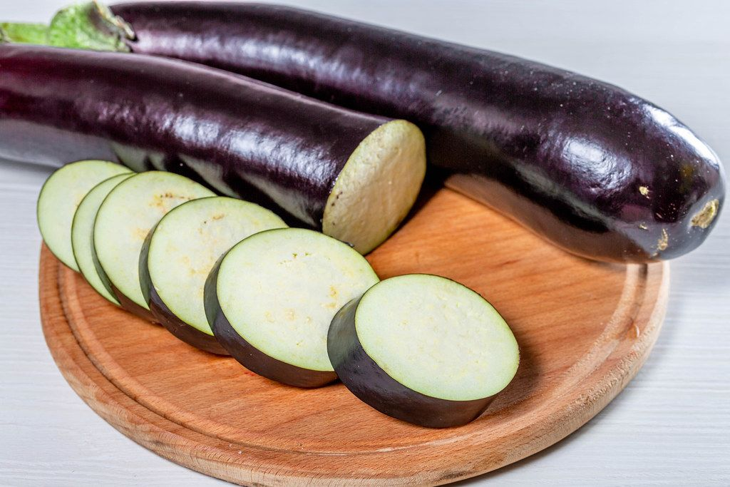 Whole and sliced ripe eggplant on the kitchen Board (Flip 2019)