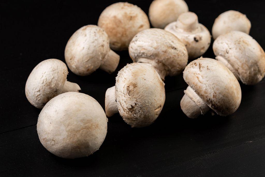 Whole mushrooms on the black background
