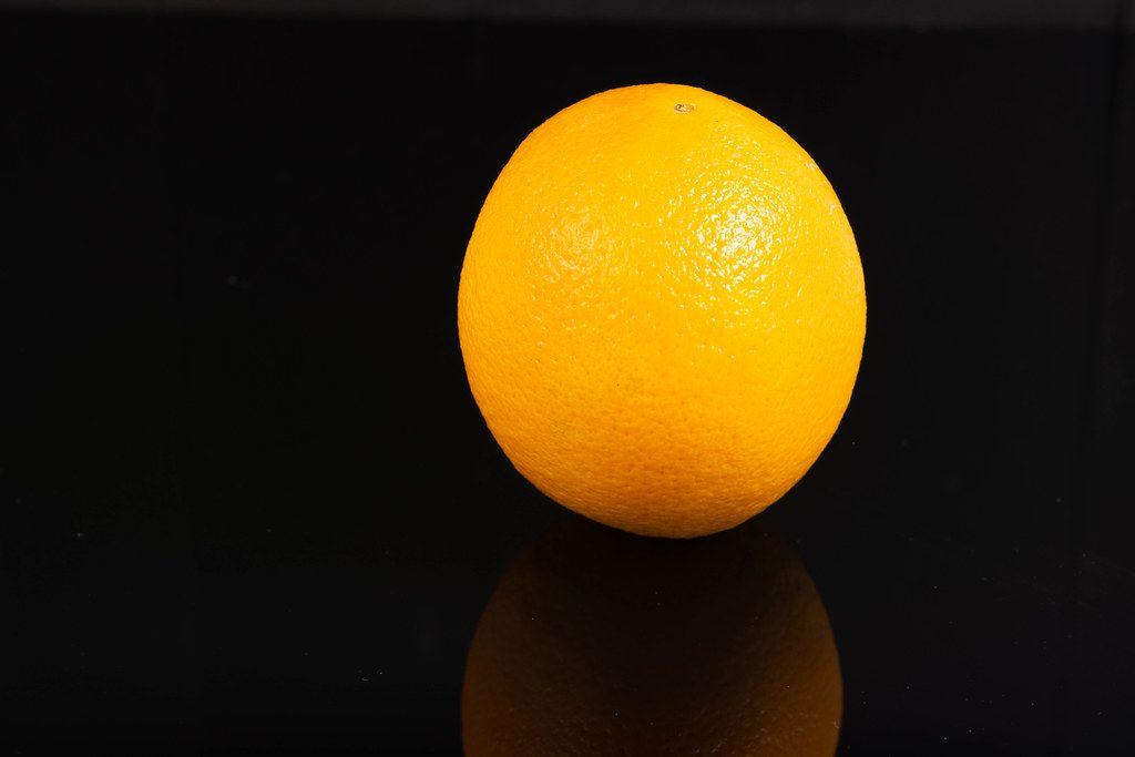 Whole Orange fruit above reflective black background