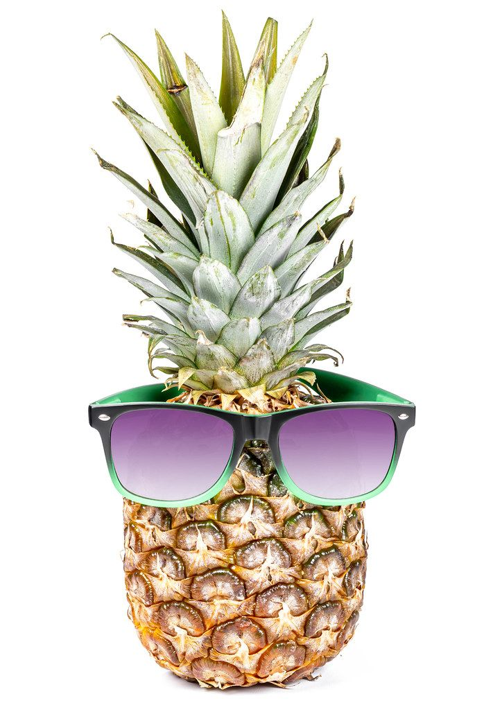 Whole raw fresh pineapple with sunglasses on white background. Summertime holiday concept
