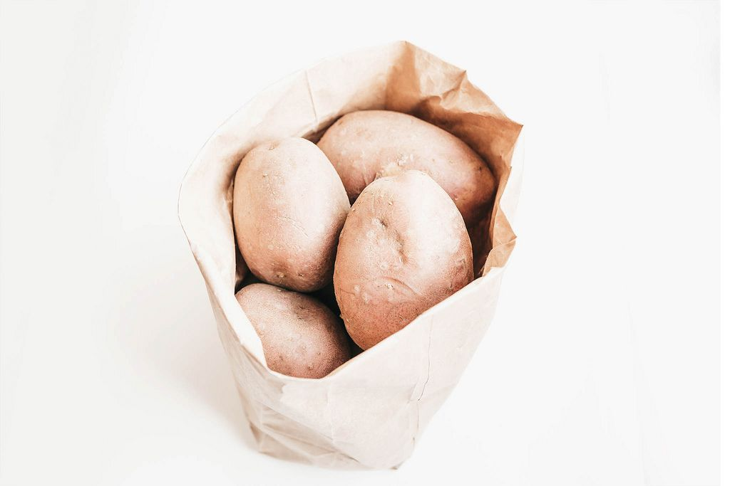 Whole raw potatoes in paper bag on white background