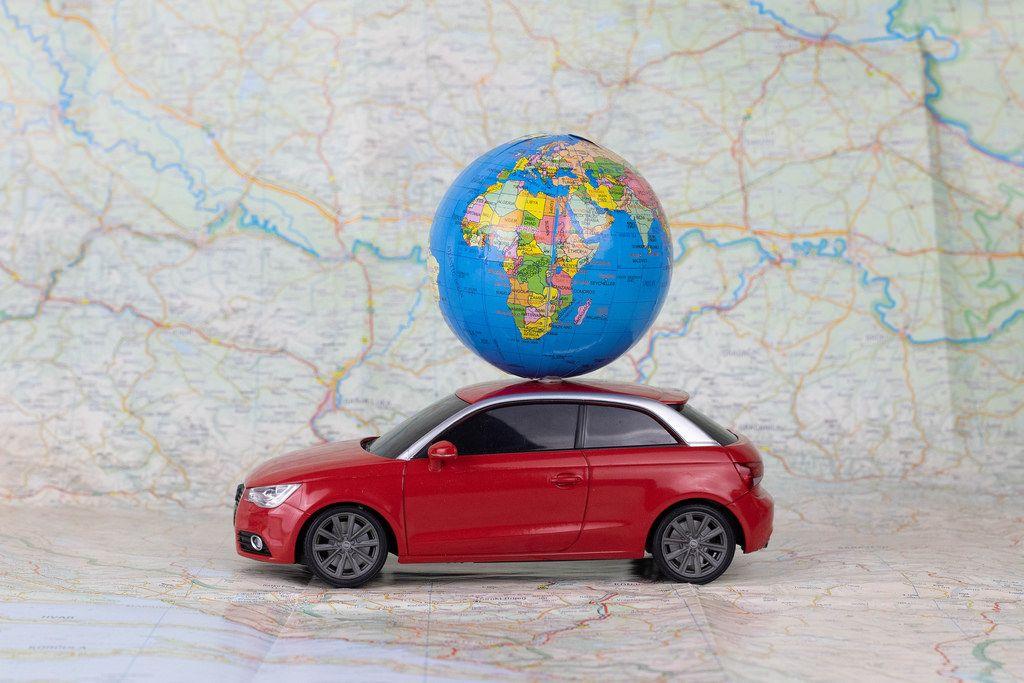 Winziges Spielzeugauto mit kleinem Globus auf dem Dach