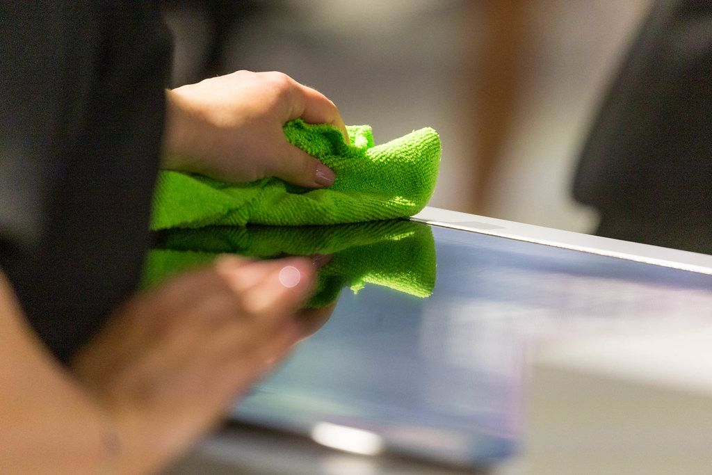 Woman cleans the kitchen surface with a green, dry cloth