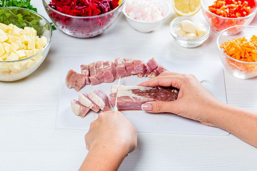 Woman cuts pork meat on white wooden table (Flip 2019)