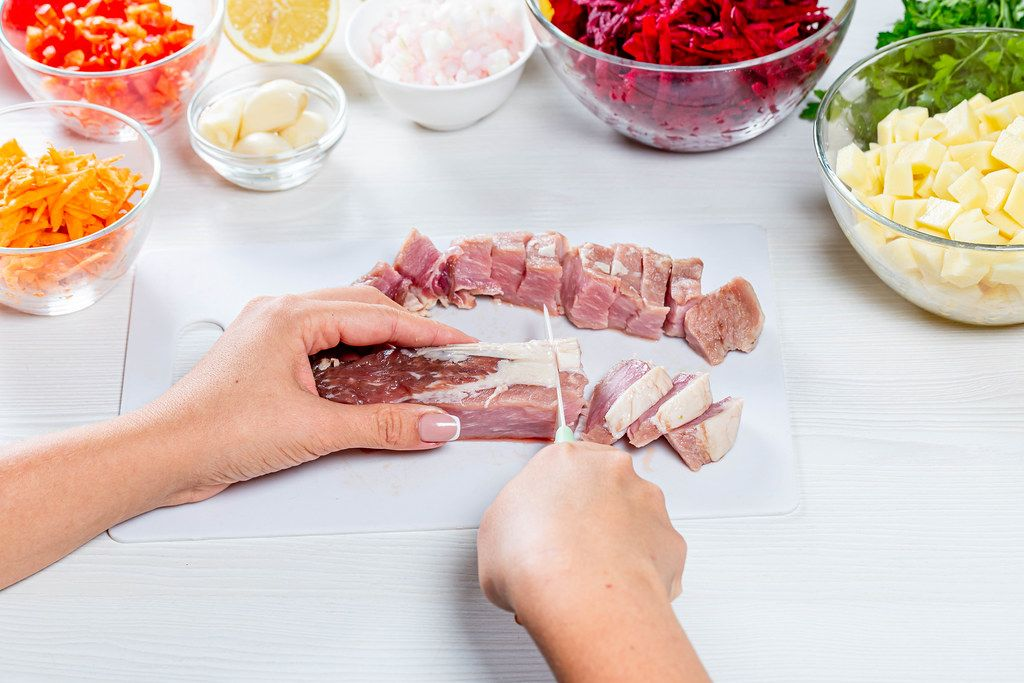 Woman cuts pork meat on white wooden table
