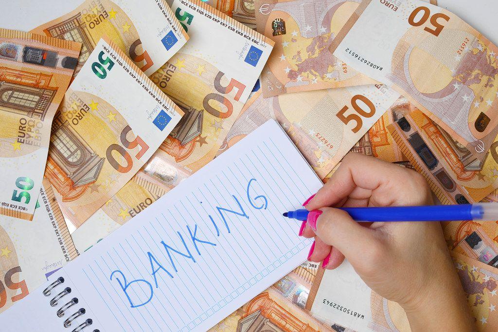Woman hand writing Banking, 50 Euro banknotes background