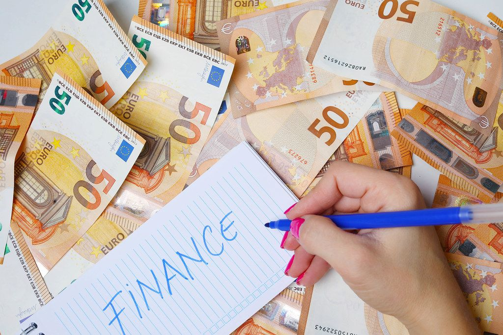 Woman hand writing Finance, 50 Euro banknotes background