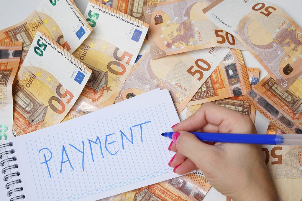Woman hand writing Payment, 50 Euro banknotes background