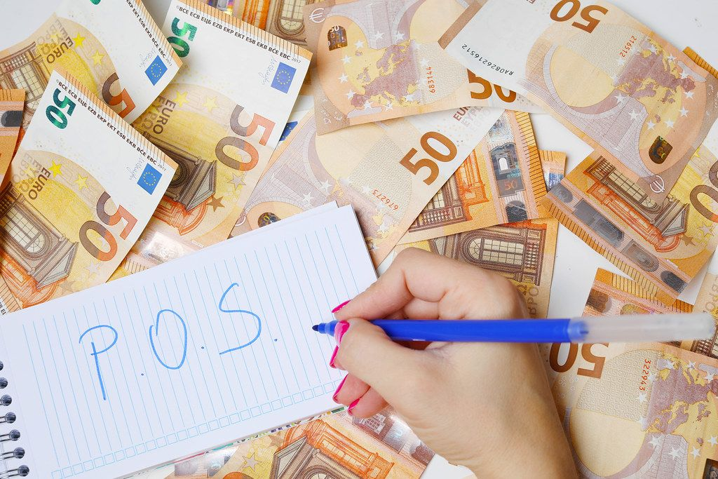 Woman hand writing POS, 50 Euro banknotes background