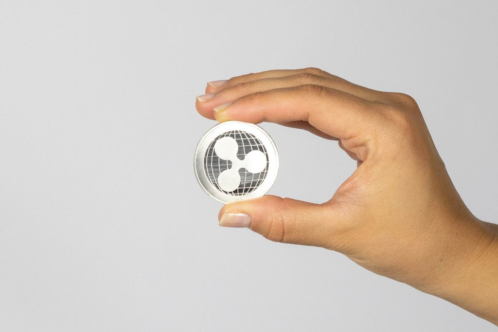 Woman holding a physical ripple coin