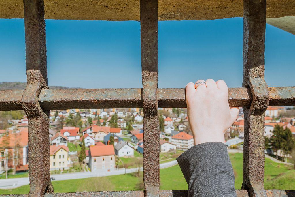 Woman holding metal bars on window