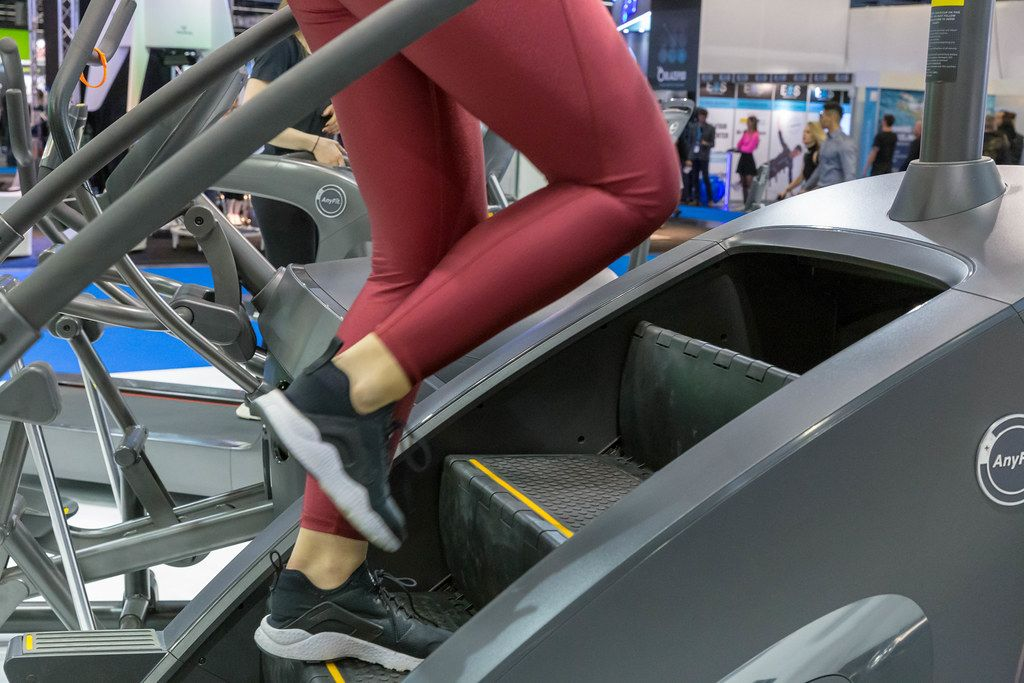 Woman in red leggings trains at an AnyFit step machine at the fitness trade show in Cologne