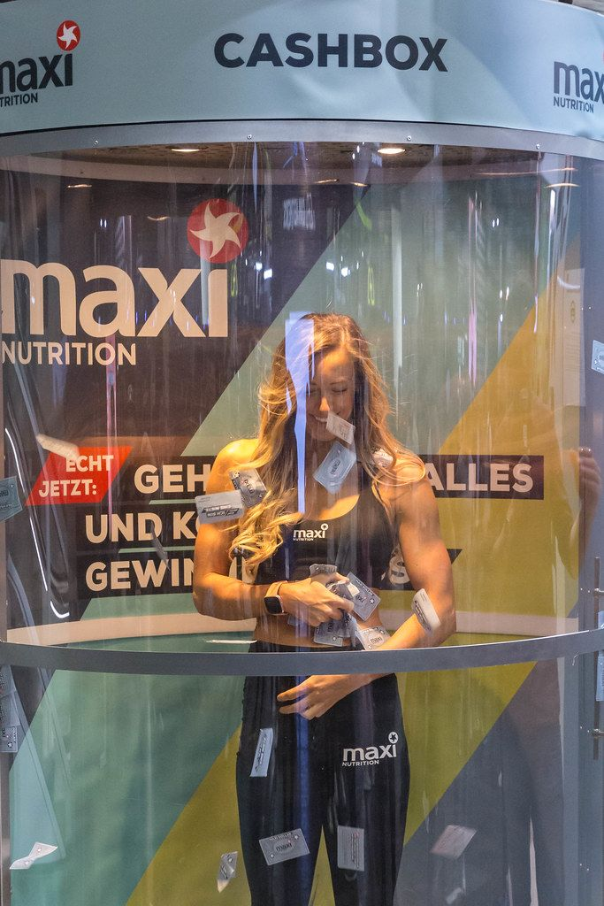 Woman in the maxi Nutrition Cashbox tries to catch cards at the fair Fibo in Cologne, Germany