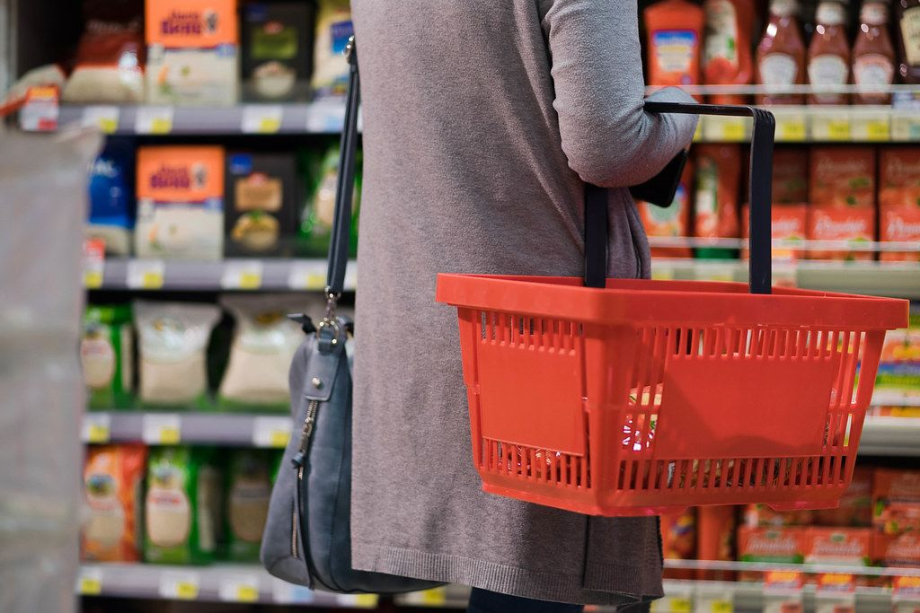 Woman standing in front of a store shelf holding a shopping basket