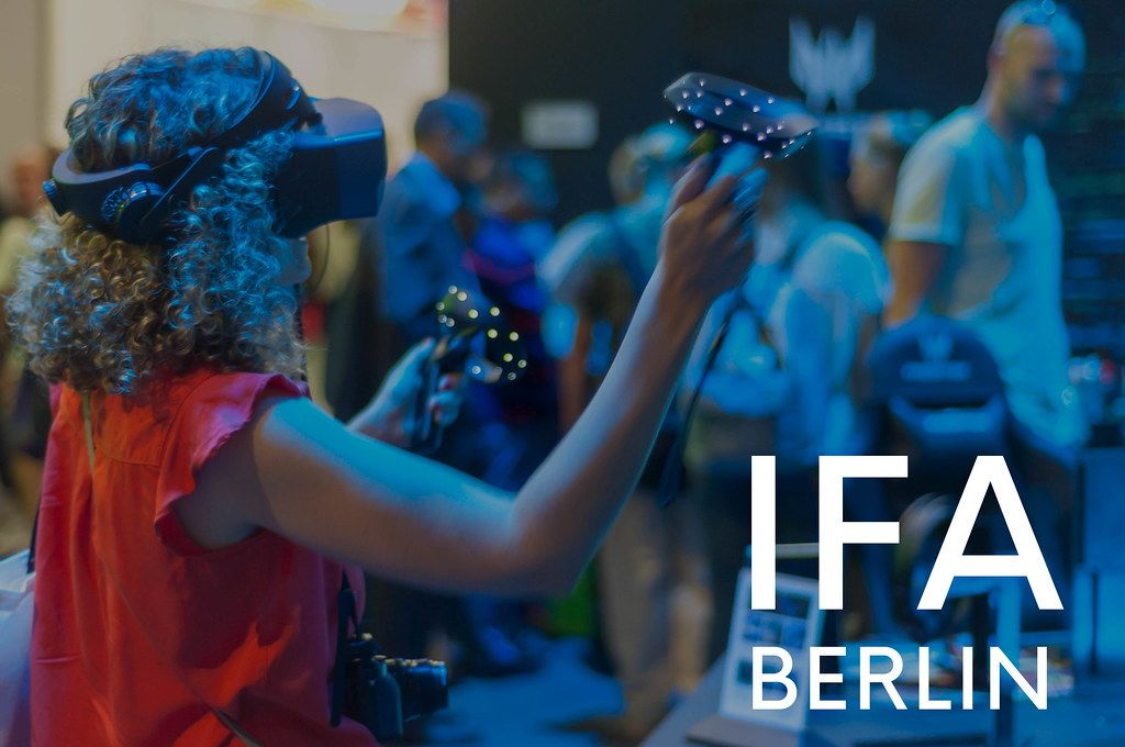 Woman with VR-Glasses on a Computer fair, next to picture title