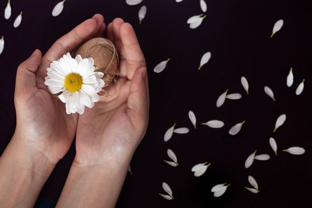 Woman's hand holding decorated Easter egg with a white flower on black background