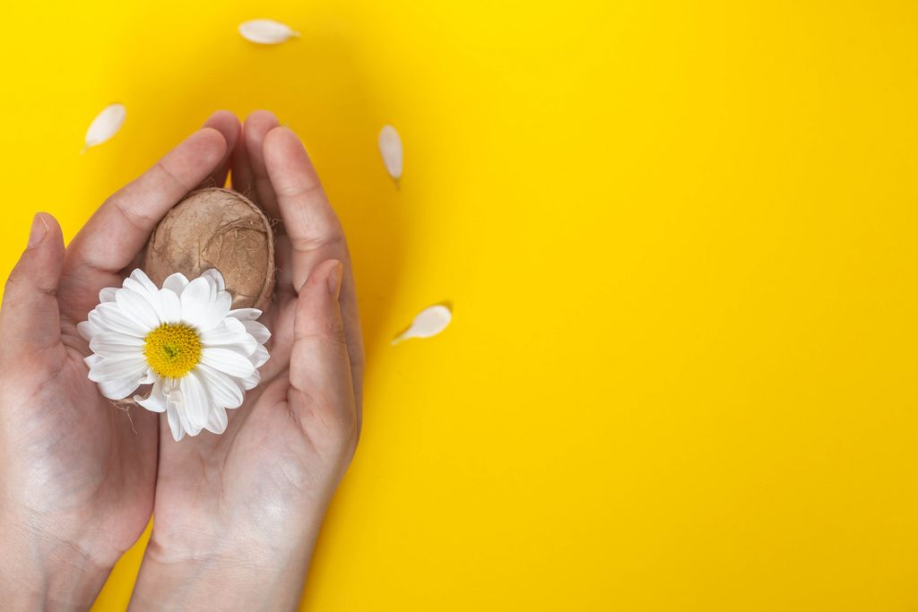 Woman's hand holding decorated Easter egg with a white flower on the bright yellow background