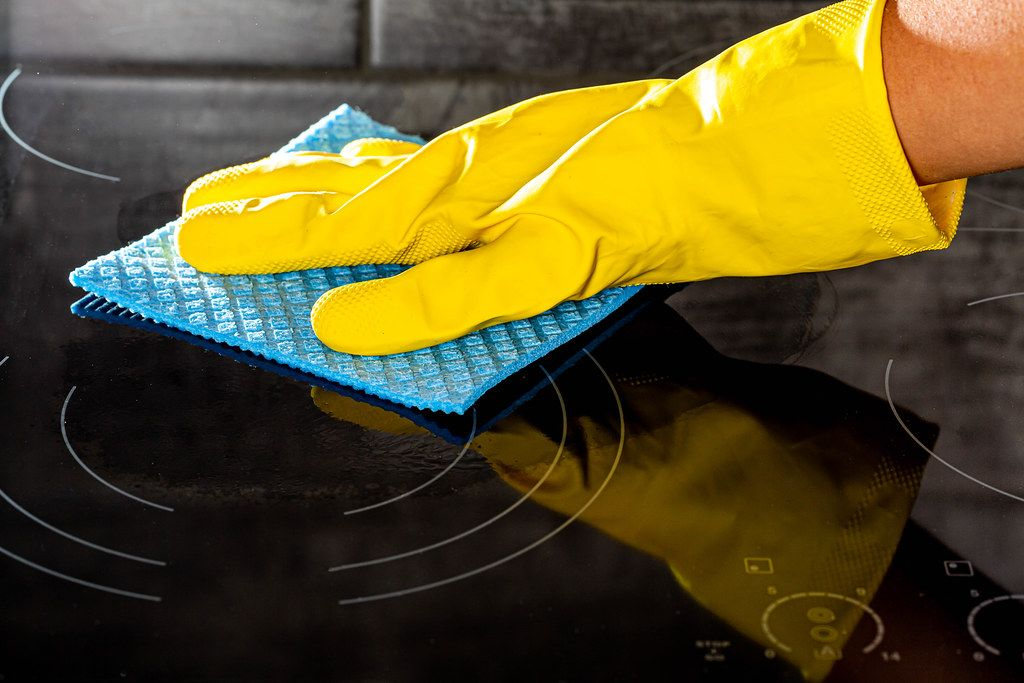 Woman's hand in a yellow rubber glove cleans the shiny electric hob. The concept of cleaning and homework