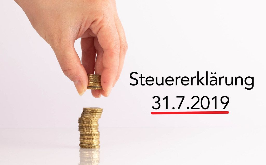 Womans hand picking up coins with Steuererklärung date