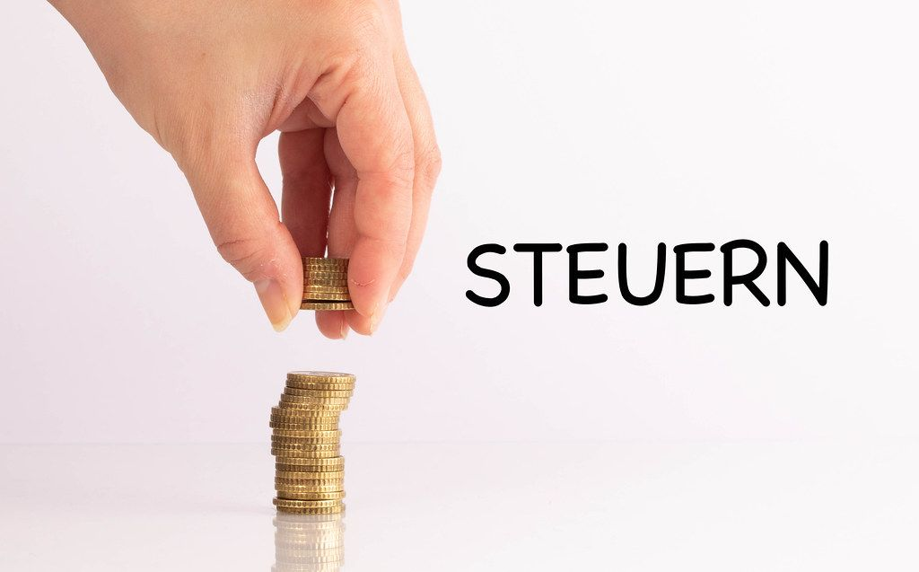 Womans hand picking up coins with Steuern text