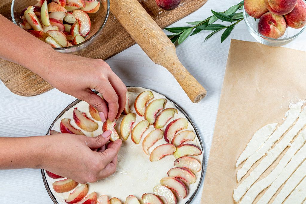 Women's hands lay pieces of peaches on the dough. Cooking peach pie (Flip 2019)