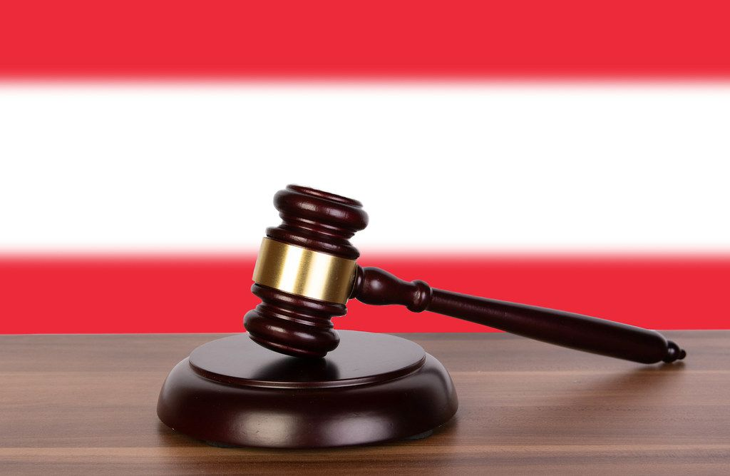 Wooden gavel and flag of Austria