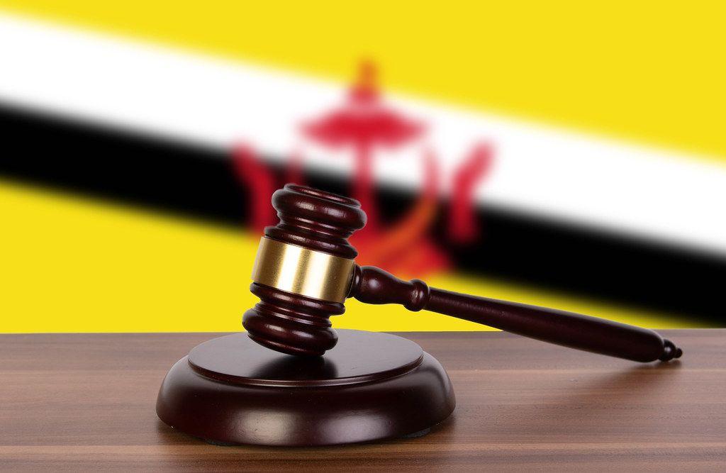 Wooden gavel and flag of Brunei