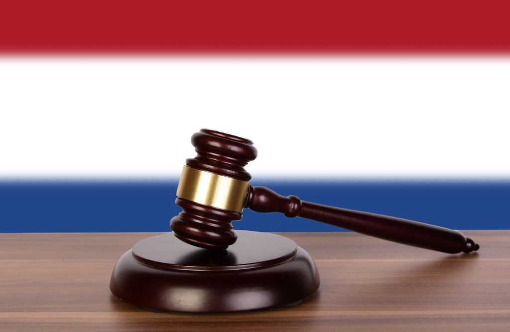 Wooden gavel and flag of Netherlands