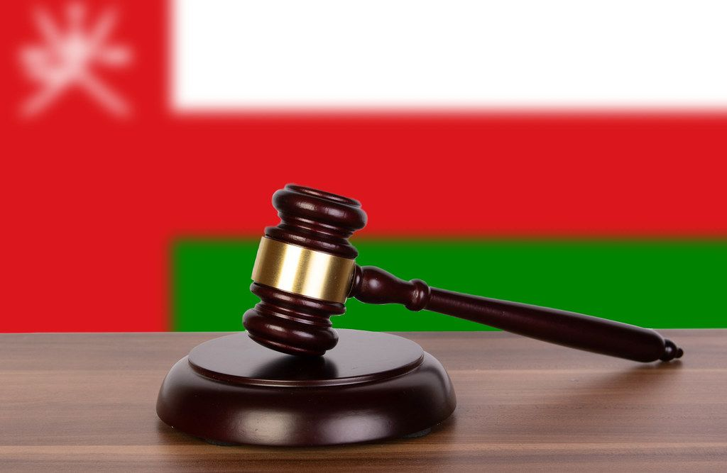 Wooden gavel and flag of Oman