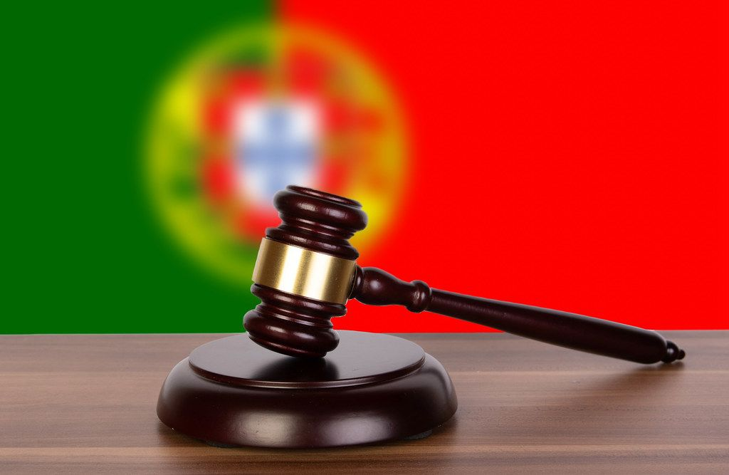 Wooden gavel and flag of Portugal