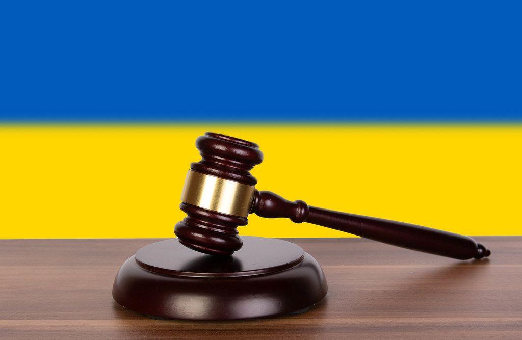 Wooden gavel and flag of Ukraine