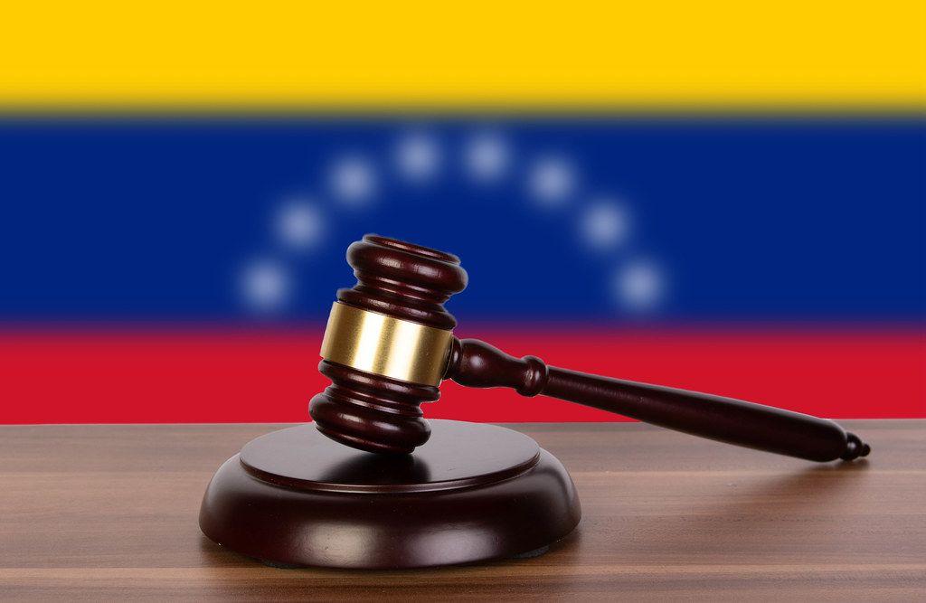 Wooden gavel and flag of Venezuela