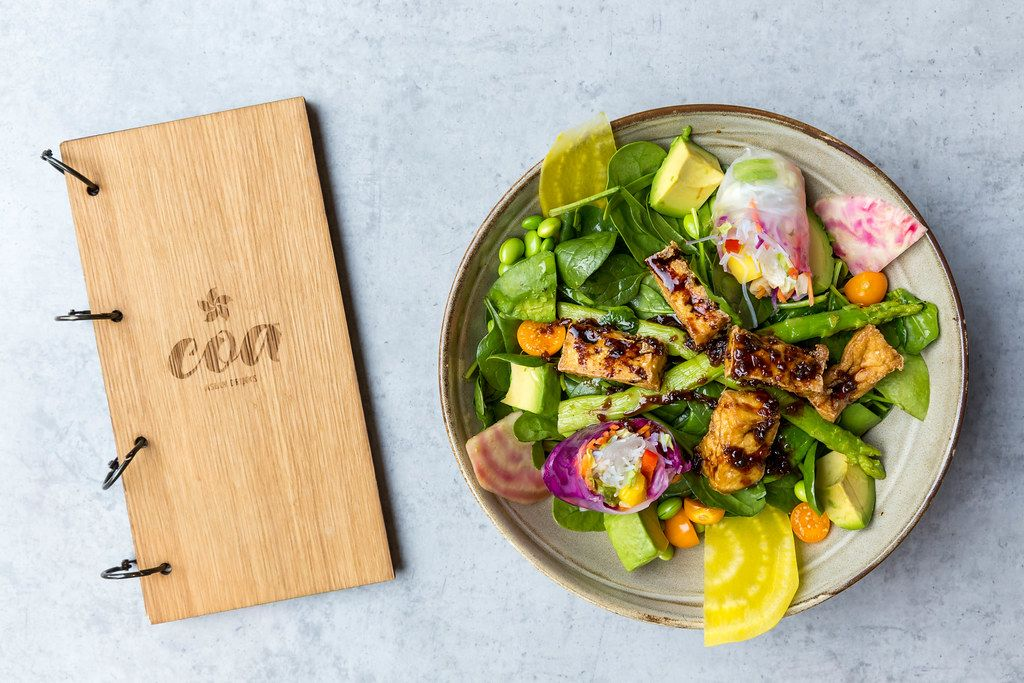Wooden menu and vegan tofu dish of the coa Wok & Bowl restaurant with tofu, baby spinach, beetroot, avocado, summer rolls, mint and raspberry-miso-dressing