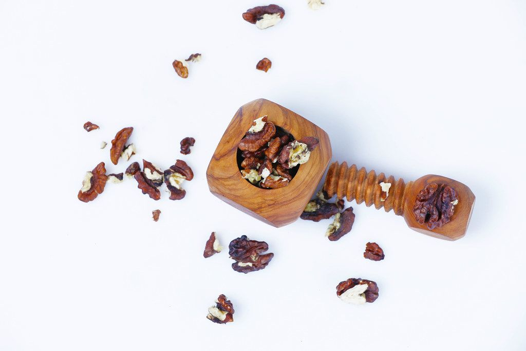 Wooden nutcracker with nuts on white background
