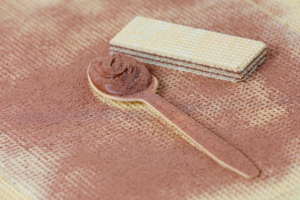 Wooden spoon filled with cocoa and chocolate cream on wafer background
